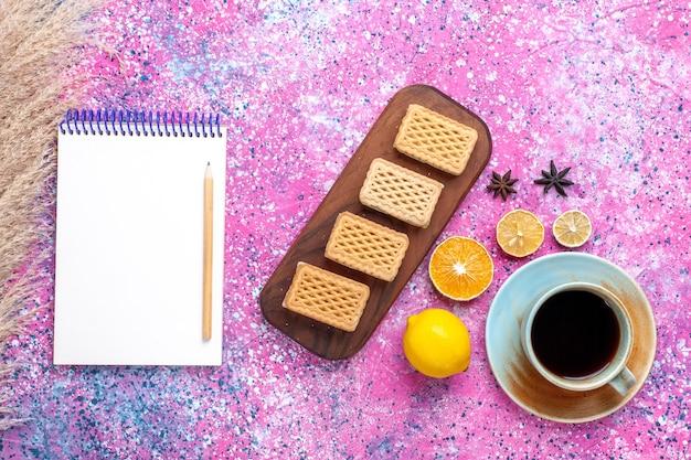 ピンクの床にレモンとクッキーとお茶のトップビューカップ。