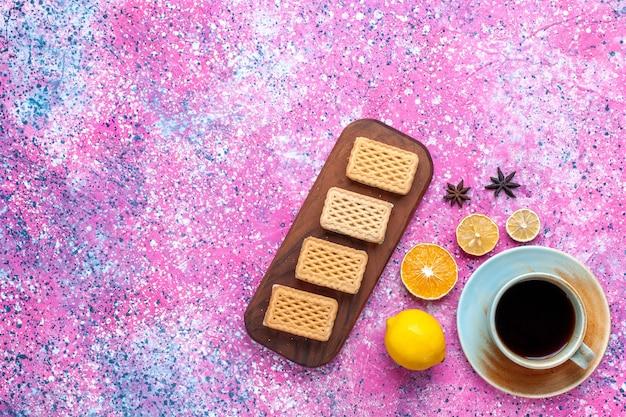 ピンクの机の上にレモンとクッキーとお茶のトップビューカップ。