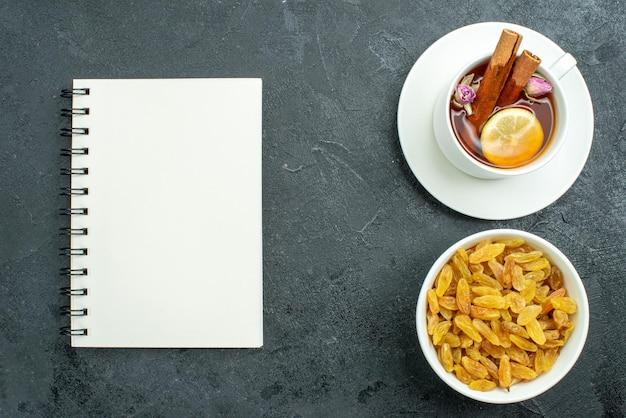 暗い表面のレーズンティーフルーツセレモニードリンクにレモンとレーズンとお茶のトップビューカップ