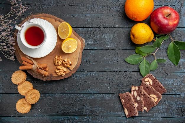 어두운 테이블에 레몬과 과자와 차의 상위 뷰 컵