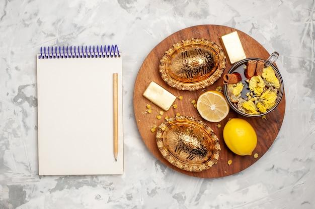 明るい白い机の上にレモンとお茶のトップビューカップ