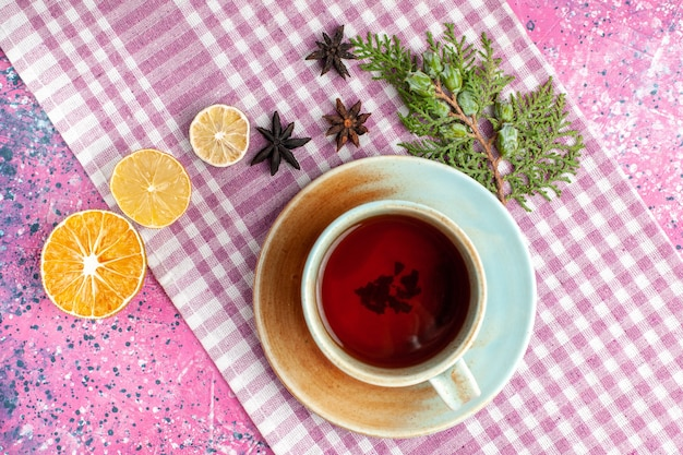 ピンクの机の上にレモンとお茶のトップビューカップ