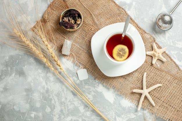 흰 벽에 레몬 조각과 차의 상위 뷰 컵 차 음료 과일 레몬