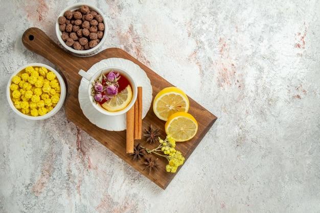 레몬 조각과 흰색 배경에 사탕과 차의 상위 뷰 컵 감귤류 차 음료