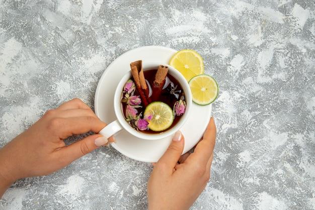 白い背景の上のレモンスライスとシナモンとお茶のトップビューカップは、熱い甘い砂糖の朝食を飲みます