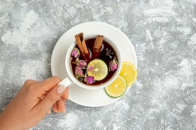 흰색 배경에 차 음료 뜨거운 달콤한 설탕 아침에 레몬 조각과 계피와 차의 상위 뷰 컵