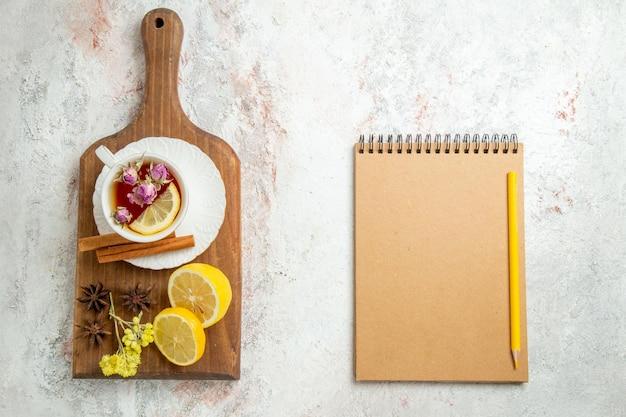 ライトホワイトの背景にレモンスライスとお茶のトップビューカップ柑橘系の果物を飲む