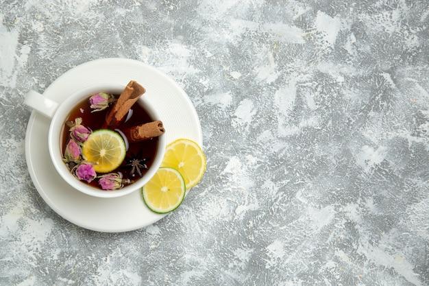 Вид сверху чашка чая с дольками лимона на белом фоне чайный напиток горячий сладкий сахарный завтрак