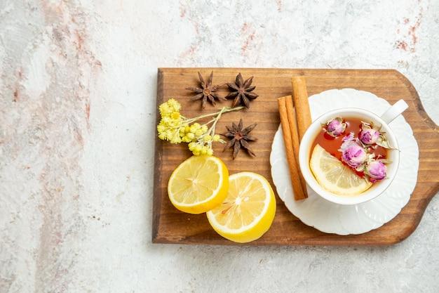 白い背景の上のレモンスライスとお茶のトップビューカップは柑橘系の果物を飲む