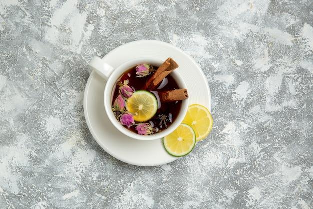 白い背景の上のレモンスライスとお茶のトップビューカップは、熱い甘い砂糖の朝食を飲みます