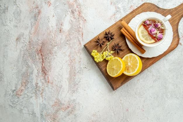 Вид сверху чашка чая с дольками лимона на белом столе чайный напиток цитрусовый