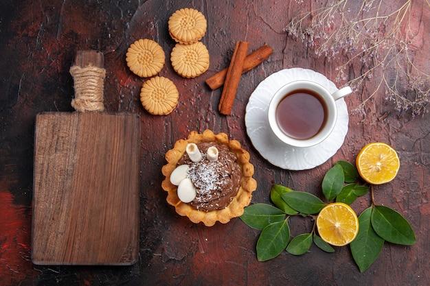 暗いテーブルの甘いデザートビスケットに小さなケーキとクッキーとお茶のトップビューカップ