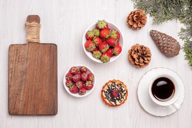 白い机の上の小さなケーキとフルーツとお茶のトップビューカップフルーツティーベリークッキーケーキ