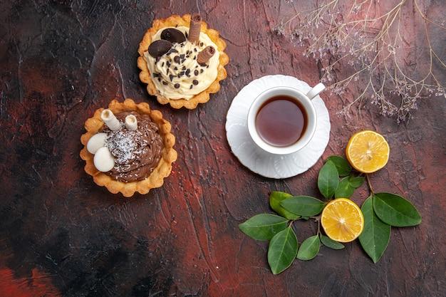 어두운 테이블 비스킷 달콤한 디저트에 작은 케이크와 차의 상위 뷰 컵