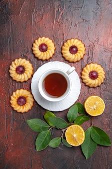 暗いテーブルのビスケットの甘いデザートに小さなクッキーとお茶のトップビューカップ