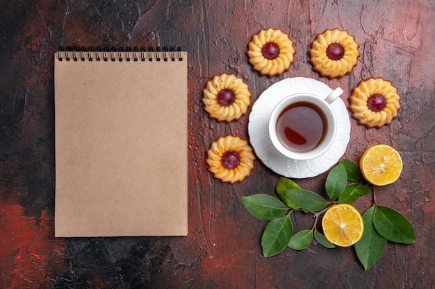 Вид сверху чашка чая с маленьким печеньем на темном столе, десерт, бисквит, сладкий