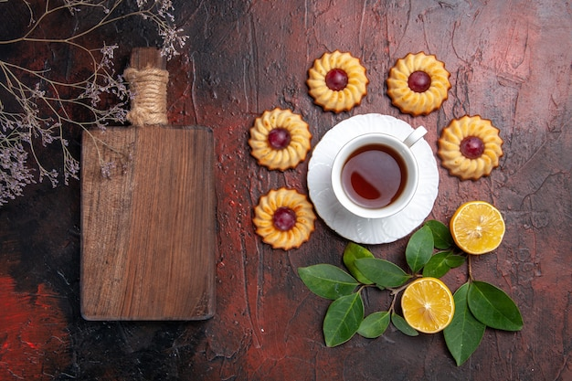 ダークテーブルのデザートビスケットスウィートに小さなクッキーとお茶のトップビューカップ