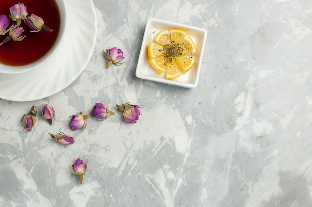 明るい白い机の上に小さな花とお茶のトップビューカップ