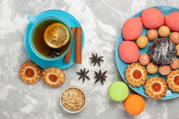 흰색 표면에 마카롱 쿠키와 케이크와 차의 상위 뷰 컵