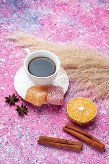 ピンクの背景にマーマレードとシナモンとお茶のトップビューカップ。