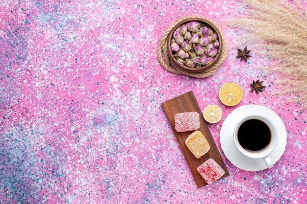 분홍색 배경에 마멀레이드와 차의 상위 뷰 컵.