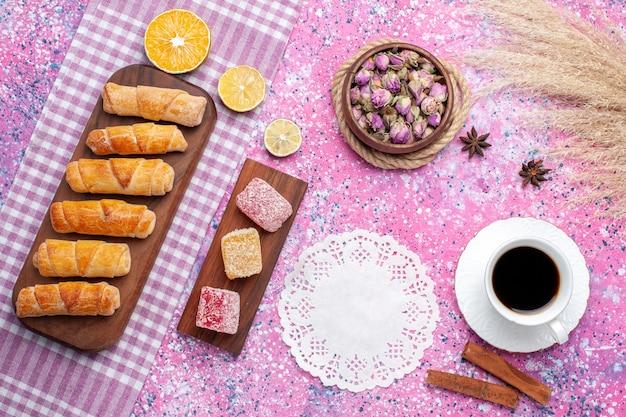 ピンクの背景にマーマレードの部分とベーグルとお茶のトップビューカップ。
