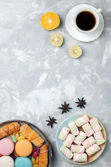 Вид сверху чашка чая с зефиром и макаронами на белом
