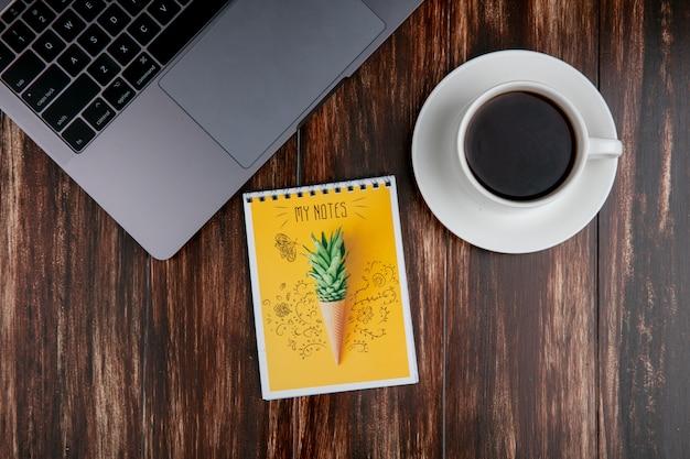 木製の背景にメモ帳とラップトップでお茶のトップビューカップ