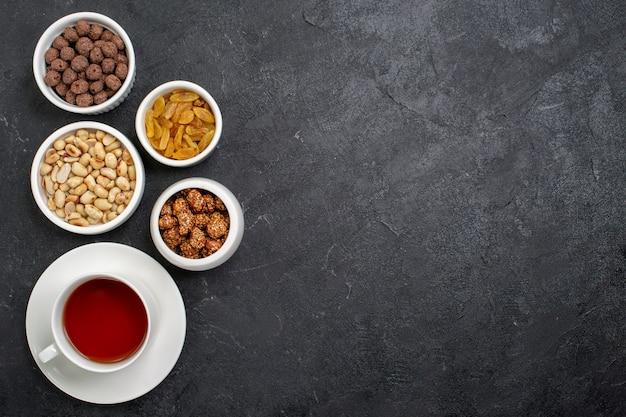 Вид сверху чашка чая с орехами и конфетами на темно-сером пространстве