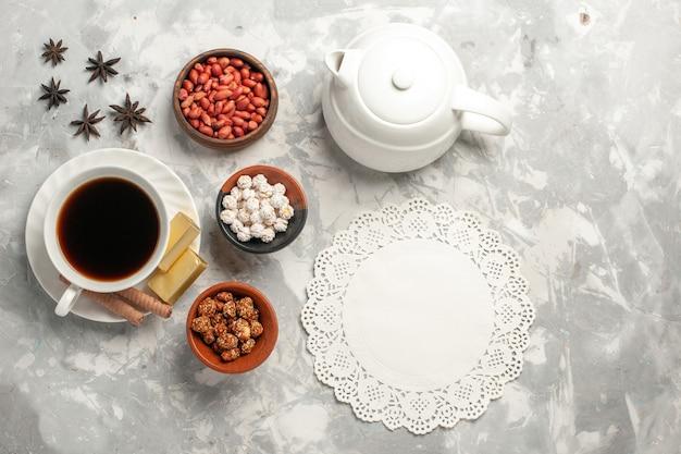 Вид сверху чашка чая с орехами и печеньем на белой поверхности