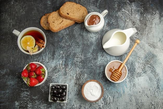 暗い表面の朝の朝食の食べ物にオリーブとフルーツとお茶のトップビューカップ