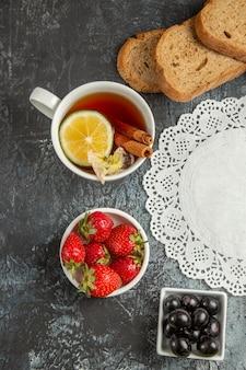 暗い表面の朝の食べ物の朝食にオリーブとフルーツとお茶のトップビューカップ