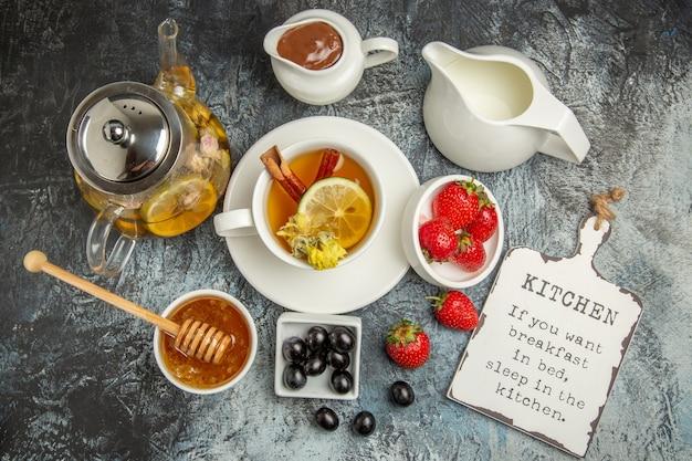 暗い表面の朝の朝食の食べ物にオリーブと蜂蜜とお茶のトップビューカップ