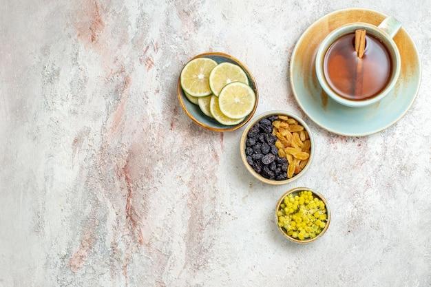 白い表面のフルーツティー柑橘類の飲み物にレーズンとレモンスライスとお茶のトップビューカップ