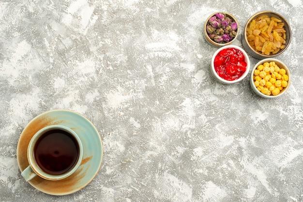 白い背景の上のレーズンとお茶のトップビューカップ甘いレーズン