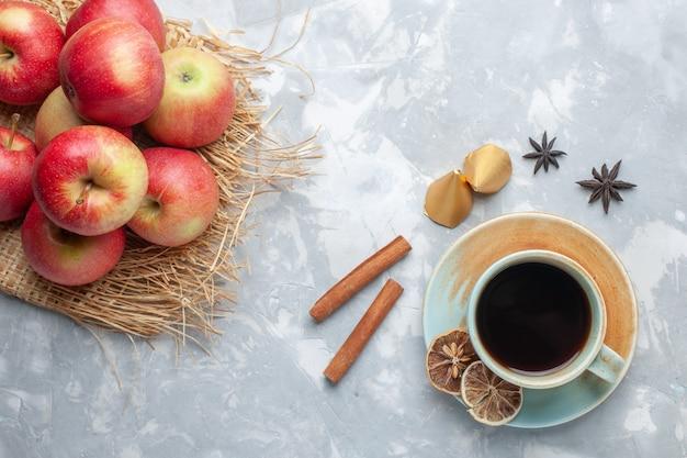 白い机の上の赤いリンゴとシナモンとお茶のトップビューのお茶のお菓子の色