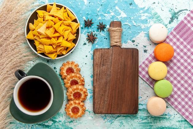 水色の背景のクッキービスケットシュガースウィートティーケーキパイにシュガークッキーとマカロンとお茶のトップビューカップ