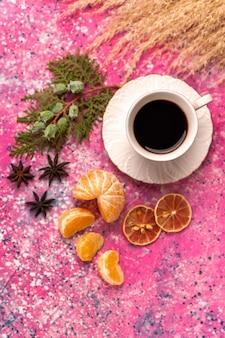 淡いピンクの机の上にみかんとお茶のトップビューカップ。
