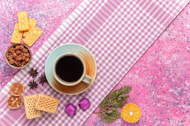 Вид сверху чашка чая с вафлями и крекерами на розовом