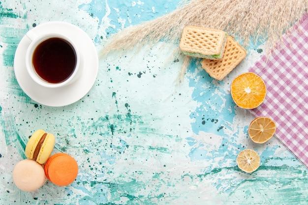 青い背景のクッキービスケットシュガー甘いケーキパイにワッフルとフレンチマカロンとお茶のトップビューカップ