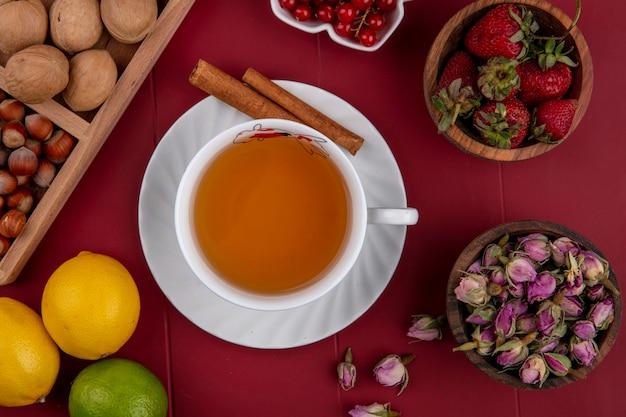 Вид сверху чашка чая с грецкими орехами с фундуком, арахисом, красной смородиной и клубникой на красном фоне