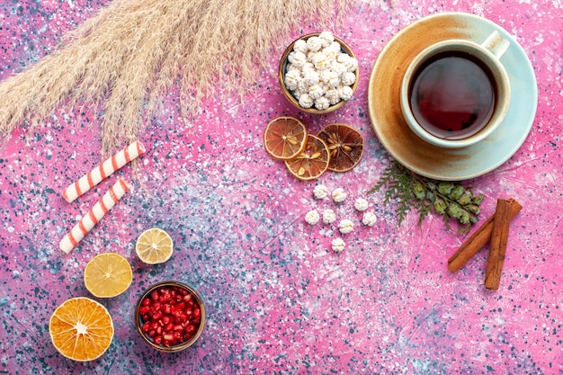 분홍색 표면에 흰색 달콤한 confitures와 계피와 차의 상위 뷰 컵