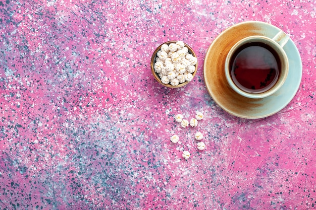 Вид сверху чашка чая с белыми сладкими конфитюрами на розовой поверхности