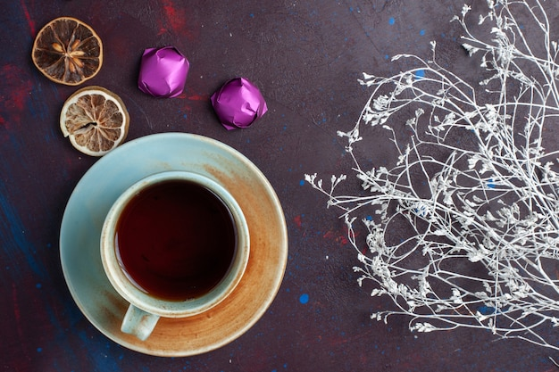 Top view of cup of tea along with chocolate candies on the dark surface