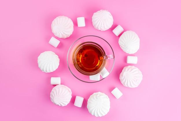 Una tazza di tè con vista dall'alto insieme a meringhe e marshmallow su caramelle rosa e zucchero