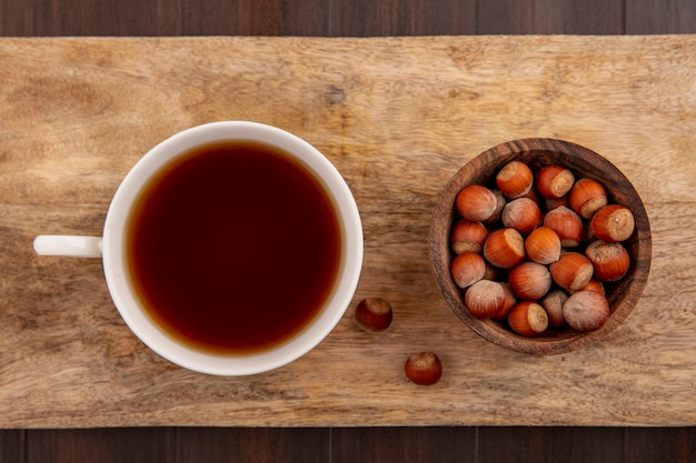 Top view of cup of tea and bowl of nuts on cutting board on wooden background