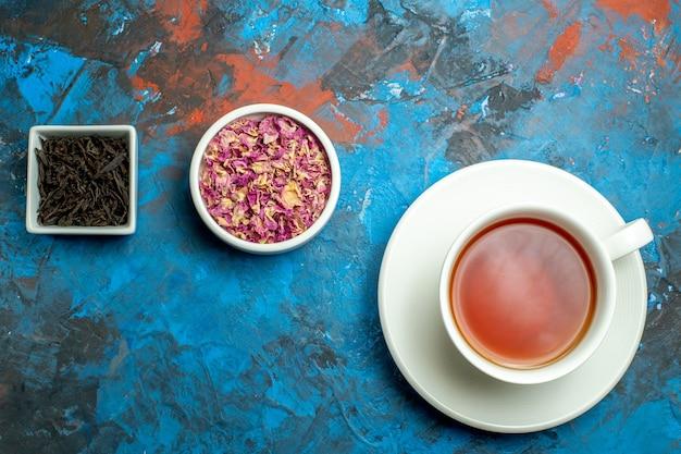 Vista dall'alto una tazza di ciotole da tè con petali di fiori secchi e tè sulla superficie rossa blu