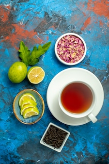 Vista dall'alto una tazza di ciotole da tè con petali di fiori secchi e fette di tè di limone sulla superficie blu rossa