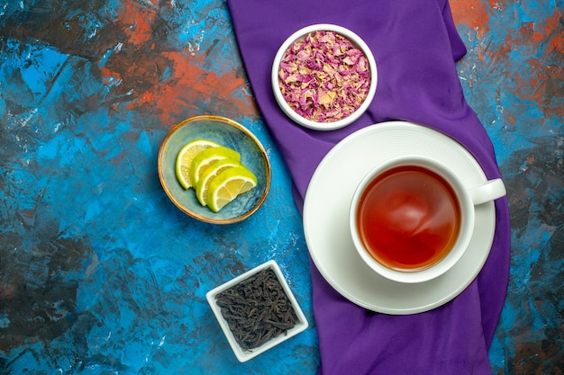 Top view a cup of tea bowls with dried flower petals and tea slices of lemon purple tablecloth on blue red surface