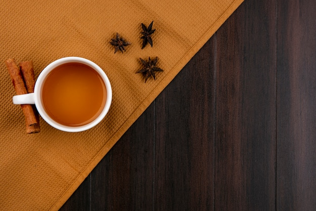 Top view of cup of tea and cinnamon on a brown towel on a wooden surface